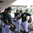 Oakland Athletics teammates right fielder Josh Reddick, left, center fielder Coco Crisp, second from left, left fielder Sam Fuld, second from right, and second baseman Eric Sogard, right, join hands in the dugout before playing the Milwaukee Brewers in a