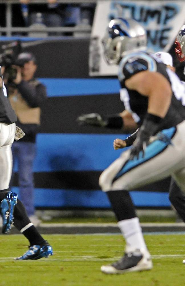 Carolina Panthers' Cam Newton, left, scrambles against the New England Patriots during the second half of an NFL football game in Charlotte, N.C., Monday, Nov. 18, 2013