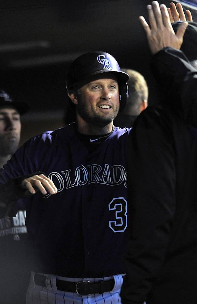 Colorado Rockies Michael Cuddyer is congratulated by his teammates after scoring in the third inning of the MLB baseball game against the Chicago White Sox on Monday, April 7, 2014, in Denver