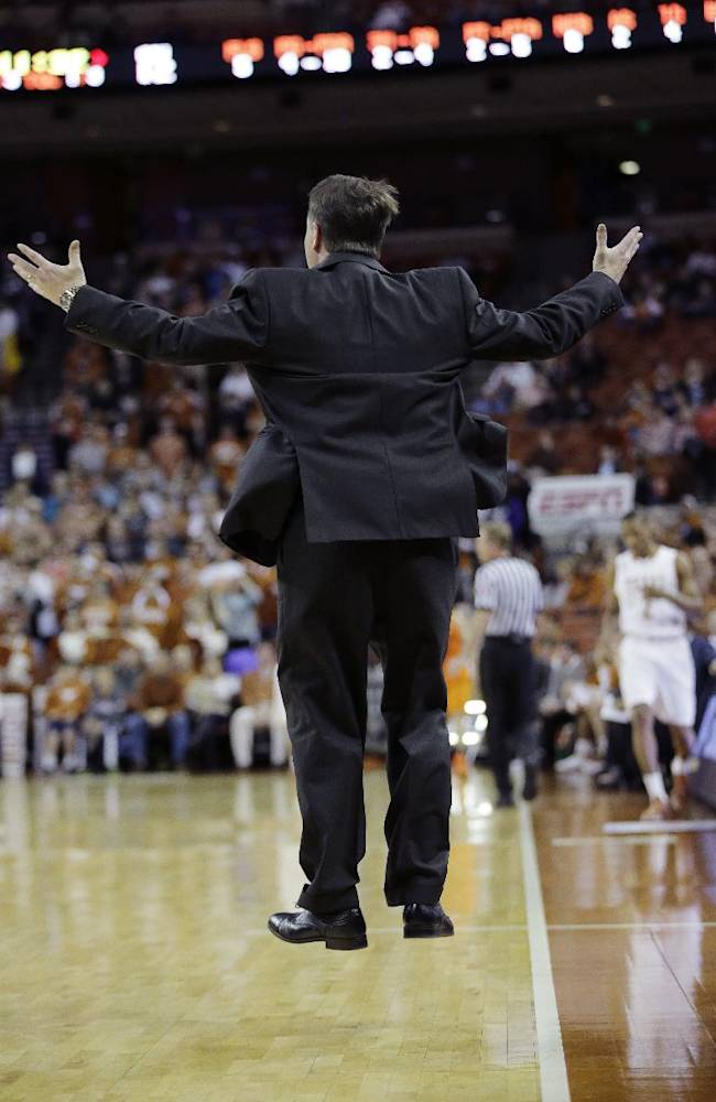 Oklahoma State coach Travis Ford jumps as he yells to his players during the first half on an NCAA college basketball game against Texas, Tuesday,  Feb. 11, 2014, in Austin, Texas