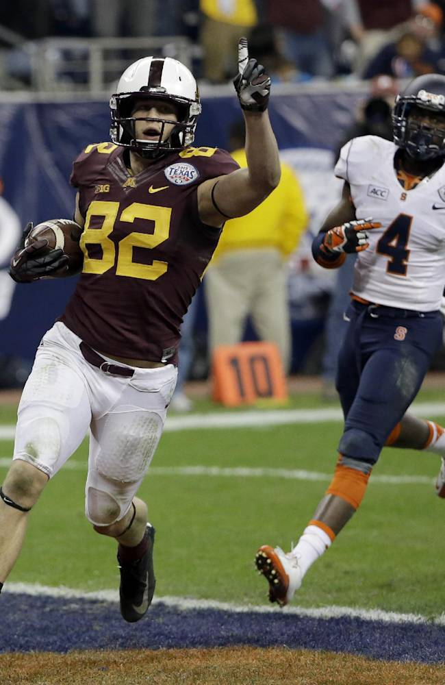 Minnesota wide receiver Drew Wolitarsky (82) celebrates after scoring a touchdown as Syracuse cornerback Brandon Reddish (4) defends during the second half of the Texas Bowl NCAA college football game on Friday, Dec. 27, 2013, in Houston. Syracuse won 21-17