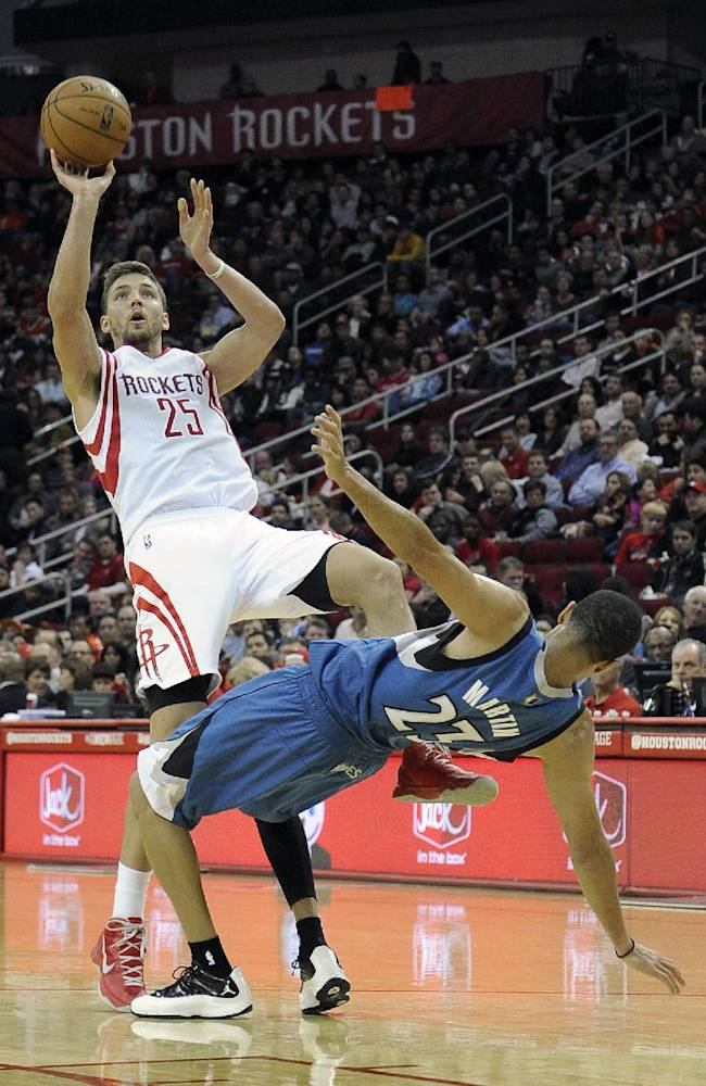 Minnesota Timberwolves' Kevin Martin (23) falls after fouling Houston Rockets' Chandler Parsons (25) in the second half of an NBA basketball game Saturday, Nov. 23, 2013, in Houston. The Rockets won 112-101