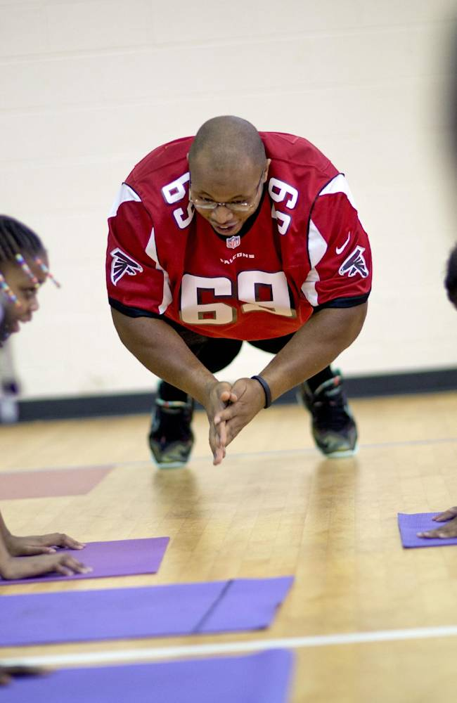Atlanta Falcons' Harland Gunn does push-ups with students from M. Agnes Jones Elementary School as the NFL football team takes part in the volunteer project,