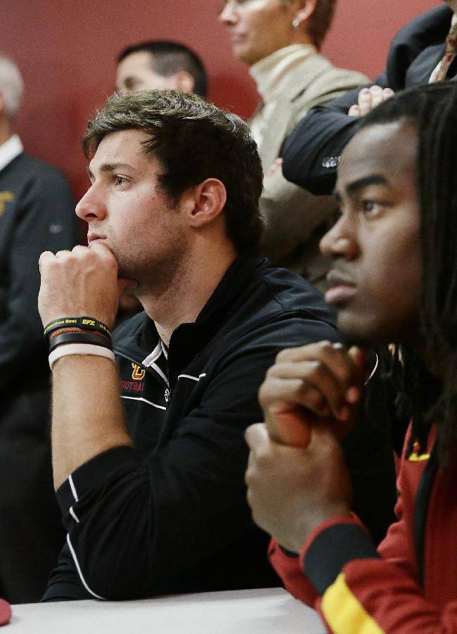 Southern California quarterback Cody  Kessler, center, and safety Josh Shaw, right, listen to their new football head coach Steve Sarkisian during a news conference on Tuesday, Dec. 3, 2013, in Los Angeles. USC hired Sarkisian away from Washington on Monday, bringing back the former Trojans offensive coordinator to his native Los Angeles area and the storied program where he thrived as Pete Carroll's assistant