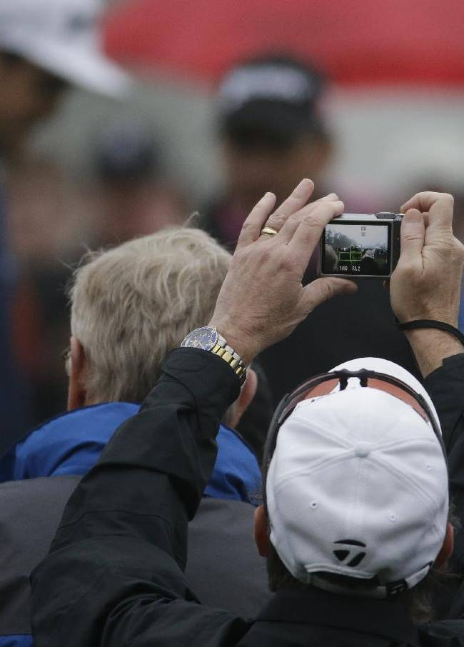 A spectator takes photos of Keegan Bradley during a practice session for the Masters golf tournament Monday, April 7, 2014, in Augusta, Ga