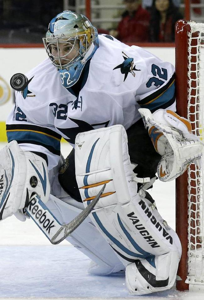 San Jose Sharks goalie Alex Stalock (32) deflects a shot on goal during the second period of an NHL hockey game against the Carolina Hurricanes in Raleigh, N.C., Friday, Dec. 6, 2013