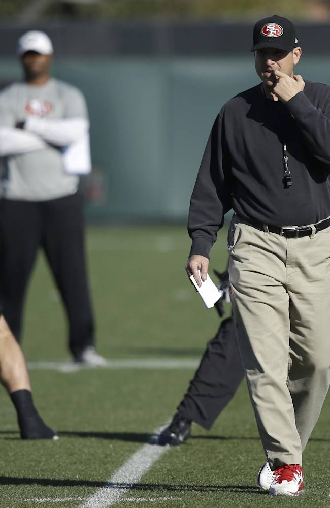 San Francisco 49ers coach Jim Harbaugh, right, walks on the field prior to an NFL football practice in Santa Clara, Calif., Friday, Jan. 17, 2014. The 49ers are scheduled to play the Seattle Seahawks for the NFC championship Sunday