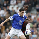Fulham's Moussa Dembele, right, competes with Everton's Gareth Barry during their English Premier League soccer match at Craven Cottage, London, Sunday, March 30, 2014