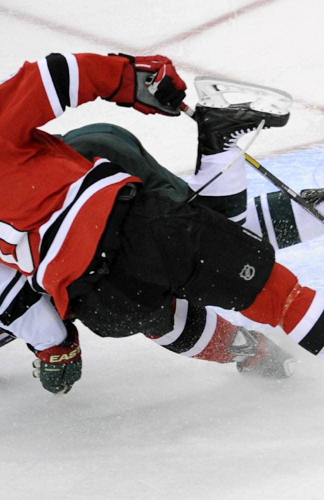 Minnesota Wild's Jonas Brodin, of Sweden, and New Jersey Devils' Dainius Zubrus (8), of Lithuania, hit the ice during the third period of an NHL hockey game Thursday, March 20, 2014, in Newark, N.J. The Devils won 4-3 in overtime