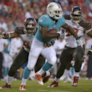 Miami Dolphins running back Damien Williams (5) is chased by Tampa Bay Buccaneers defensive tackles Gerald McCoy (93) and Clinton McDonald (98) on a run during the second quarter of an NFL preseason football game Saturday, Aug. 16, 2014, in Tampa, Fla The