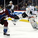 San Jose Sharks goalie Alex Stalock, right, clears puck from behind net as Colorado Avalanche left wing Gabriel Landeskog, of Sweden, covers in the first period of an NHL hockey game on Saturday, March 29, 2014, in Denver The Associated Press