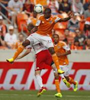 Houston Dynamo's Oscar Boniek Garcia (27) heads the ball over the New York Red Bulls' Dax McCarty during the first half of an MLS Eastern Conference semifinal playoff match, Sunday, Nov. 3, 2013, in Houston. (AP Photo/Eric Christian Smith)