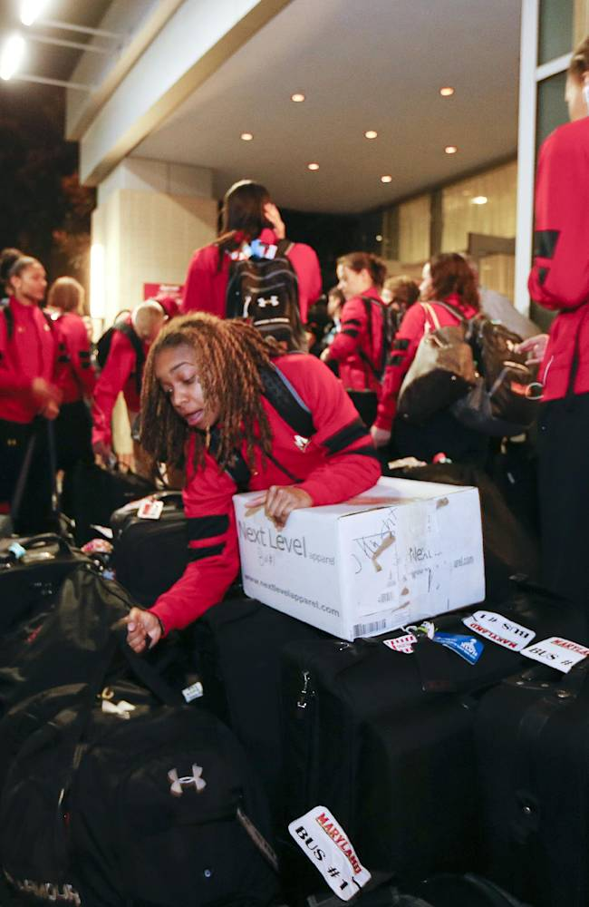 Maryland guard Sequoia Austin, center, gets her bag as the team arrives at their hotel for the NCAA women's Final Four college basketball tournament Thursday, April 3, 2014, in Nashville, Tenn. Maryland is scheduled to play Notre Dame in a semifinal on Sunday