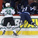 Dallas Stars' Vernon Fiddler (38) checks Winnipeg Jets' TJ Galiardi (21) into his own bench during the first period of an NHL hockey game in Winnipeg, Manitoba, on Saturday, Jan. 31, 2015 The Associated Press