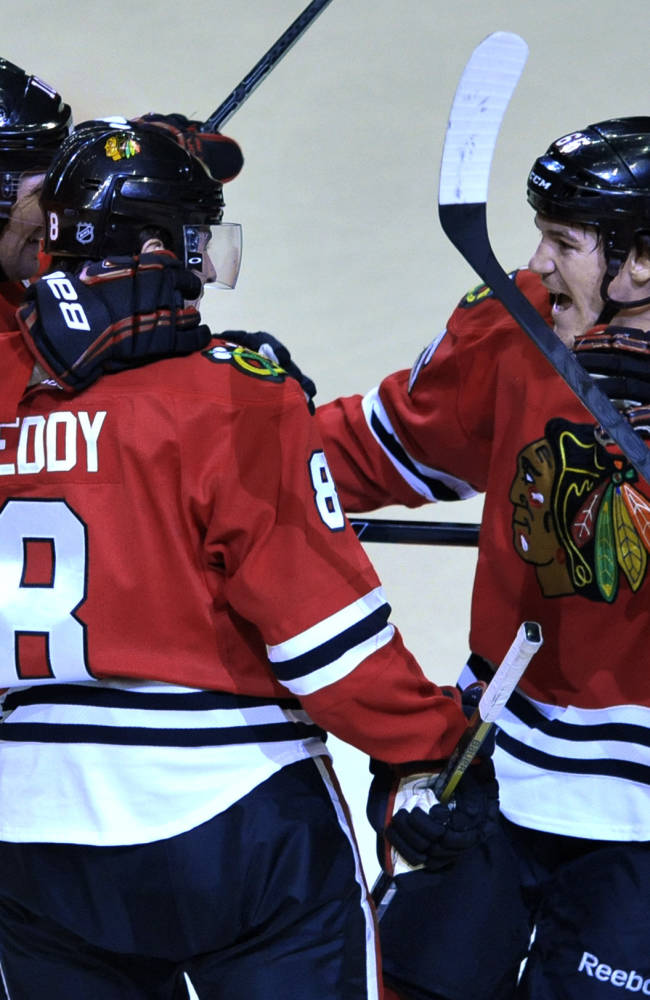 Chicago Blackhawks' Andrew Shaw (65), celebrates with teammates Nick Leddy (8), and Patrick Sharp (10), after scoring during the second period of an NHL hockey game against the St. Louis Blues in Chicago, Wednesday, March, 19, 2014