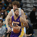 Los Angeles Lakers guard Kendall Marshall, front, looks to pass ball under pressure from Denver Nuggets forward Jan Vesely, of the Czech Republic, in the fourth quarter of the Nuggets' 134-126 victory in an NBA basketball game in Denver on Friday, March 7