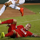 AS Roma's Marco Borriello (9) leaps over Liverpool FC defender Martin Skrtel, bottom, after challenging for the ball during a friendly soccer match at Fenway Park in Boston, Wednesday, July 23, 2014. AS Roma won 1-0. (AP Photo)