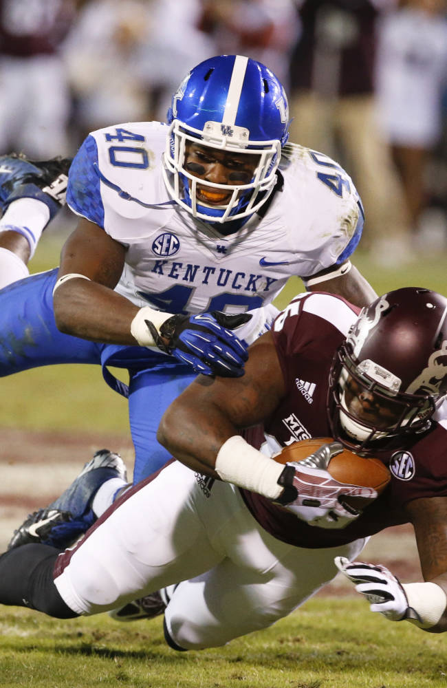 Mississippi State tight end Artimas Samuel (85) protects his pass reception as Kentucky linebacker Avery Williamson (40)dives on him in the second half of their NCAA college football game at Davis Wade Stadium in Starkville, Miss., Thursday, Oct. 24, 2013. Mississippi State won 28-22