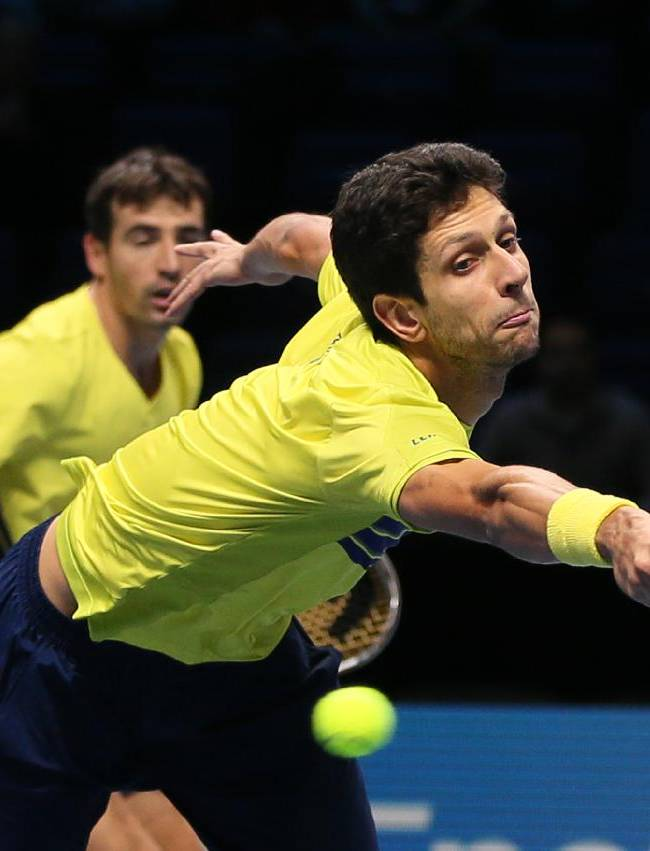Marcelo Melo of Brazil, right, watched by partner Ivan Dodig of Croatia, stretches and fails to reach a return to David Marrero of Spain and Fernando Verdasco of Spain during their ATP world Tour Finals semifinal tennis match at the O2 Arena on London, Sunday, Nov. 10, 2013