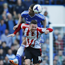 Chelsea's Gary Cahill, top, jumps for the ball with Sunderland's Connor Wickham during their English Premier League soccer match at the Stamford Bridge ground in London, Saturday April 19, 2014