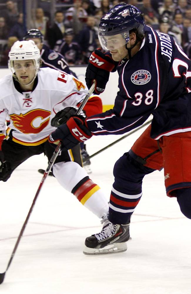 Columbus Blue Jackets' Boone Jenner (38) battles for the puck against Calgary Flames' Kris Russell in the second period of an NHL hockey game in Columbus, Ohio, Friday, Oct. 4, 2013