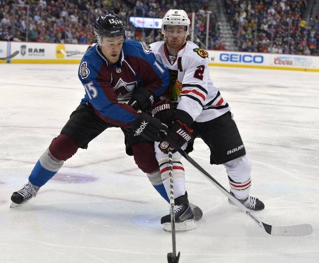 Colorado Avalanche right wing P.A. Parenteau (15) and Chicago Blackhawks defenseman Duncan Keith (2) chase the puck into the corner during the second period of an NHL hockey game Tuesday, Nov. 19, 2013, in Denver