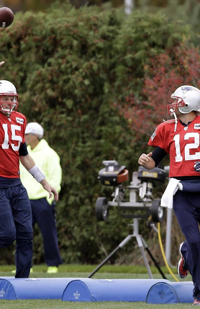 New England Patriots quarterbacks Tom Brady (12) and Ryan Mallett (15) toss a ball back-and-forth at the NFL football team's facility in  Foxborough, Mass., Wednesday, Oct. 23, 2013. The Patriots will play the Miami Dolphins Sunday