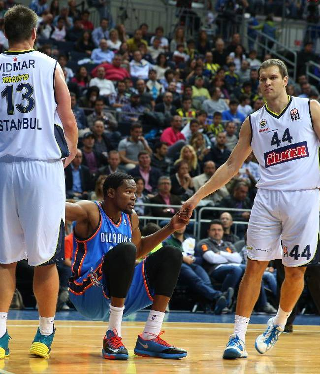 The NBA team Oklahoma City Thunder's Kevin Durant, center, is helped up by Gasper Vidmar and Bojan Bogdanovic of Fenerbahce Ulker during a preseason basketball game in Istanbul, Turkey, Saturday, Oct. 5, 2013. Oklahoma City Thunder has opened the preseason schedule with a game against the five-time Turkish champions at the Ulker Sports Arena.(AP Photo)