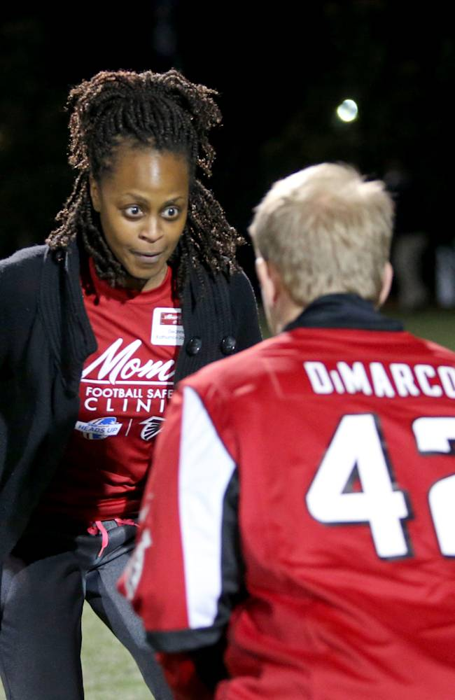 Deanna Kathumbi-Jackson, rear, of Sandy Springs, Ga., participates in a drill with Atlanta Falcons fullback Patrick DiMarco during a youth football safety clinic at Kings Ridge Christian School on Tuesday, March 18, 2014, in Alpharetta, Ga. The purpose was to educate mothers on concussion symptoms, proper tackling techniques and correct fitting of helmets and pads as the NFL seeks to keep the sport growing amid lawsuits brought by former players during the last few years