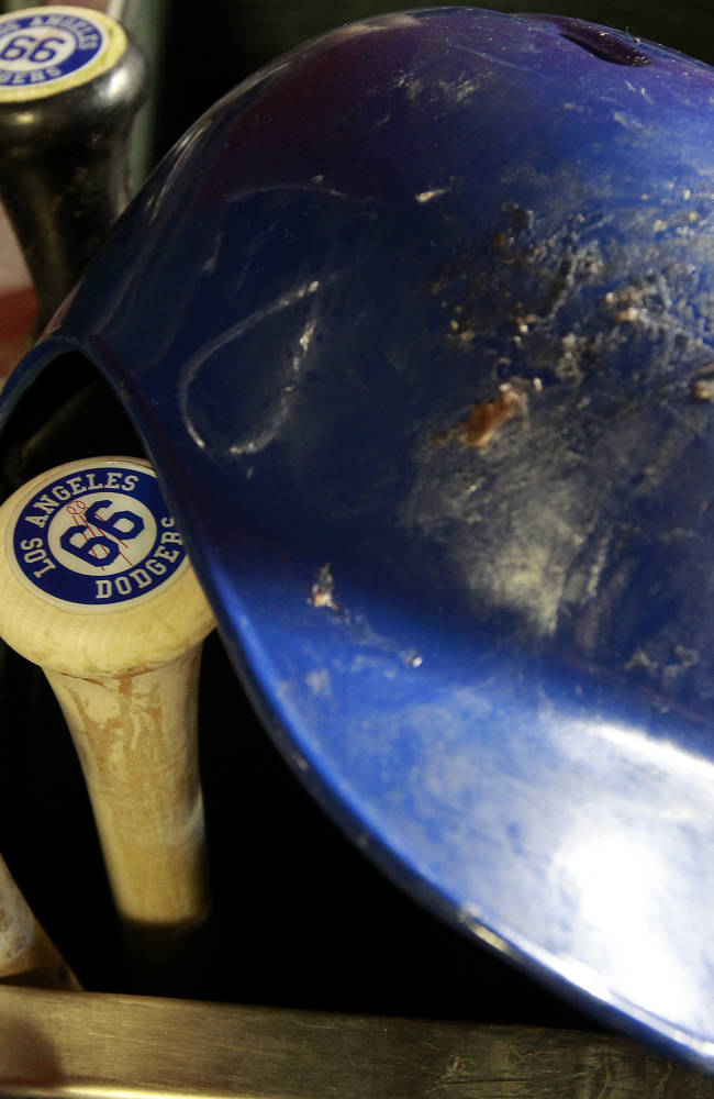 The helmet and bats of Los Angeles Dodgers' Yasiel Puig sit in the dugout before the start of a baseball game against the Arizona Diamondbacks on Saturday, April 12, 2014, in Phoenix. The Dodgers defeated the Diamondbacks 8-5