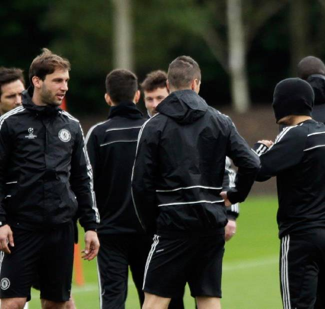 Chelsea's Eden Hazard, right, stands with his hat pulled down over his face, next to Fernando Torres, center, and Branislav Ivanovic, left, as they gather together at the start of a training session at their facilities, in Stoke d'Abernon, near London, Monday, April 7, 2014.  Paris Saint-Germain take a 3-1 lead from the first leg into their second leg Champions League quarterfinal soccer match against Chelsea on Tuesday