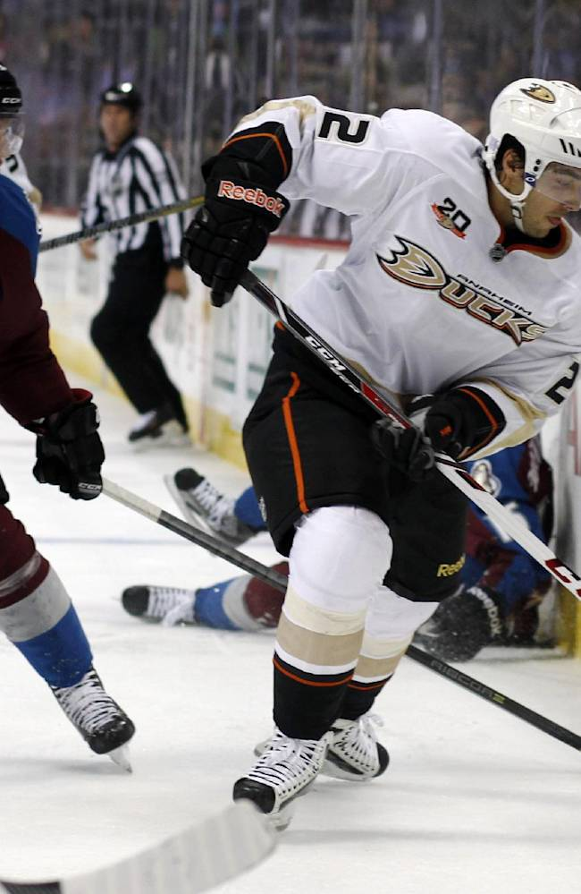 Anaheim Ducks center Mathieu Perreault, right, takes control of the puck along the boards as Colorado Avalanche center Nathan MacKinnon covers in the second period of an NHL hockey game in Denver, Wednesday, Oct. 2, 2013