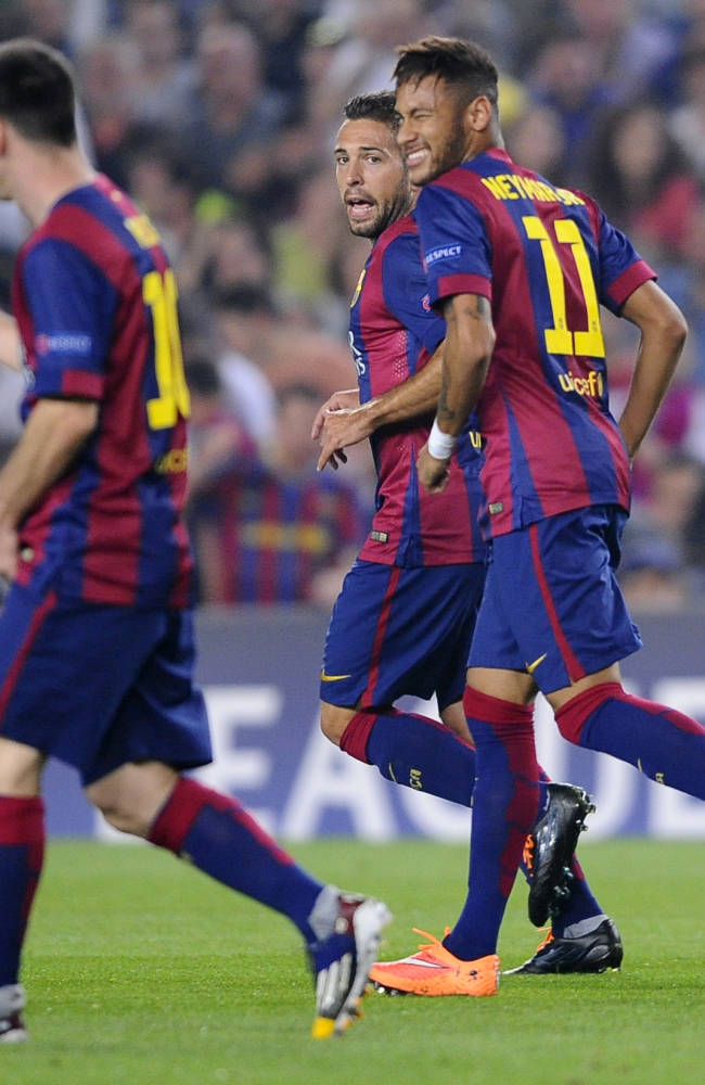 Barcelona's Neymar, right, winks at his teammate Lionel Messi, left, as Jordi Alba looks on after Neymar scored during the Champions League group F soccer match between F.C. Barcelona and Ajax at the Camp Nou stadium in Barcelona, Spain, Tuesday, Oct. 21, 2014