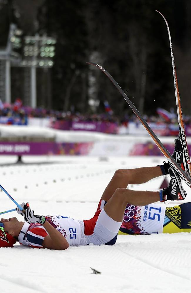 Norway's Chris Andre Jespersen, left, wears a cut suit as he takes some rest after completing the men's 15K classical-style cross-country race at the 2014 Winter Olympics, Friday, Feb. 14, 2014, in Krasnaya Polyana, Russia