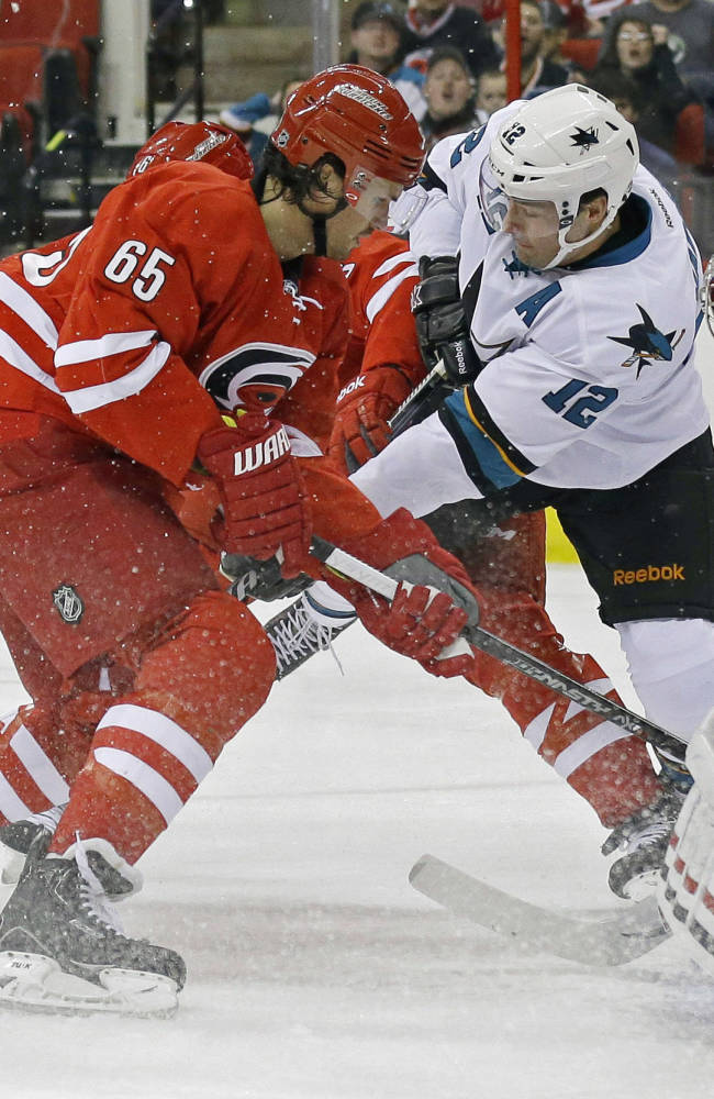 Carolina Hurricanes' Ron Hainsey (65) and goalie Cam Ward defend against San Jose Sharks' Patrick Marleau (12) during the first period of an NHL hockey game in Raleigh, N.C., Friday, Dec. 6, 2013