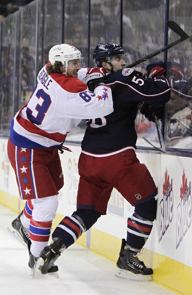 Washington Capitals' Jay Beagle, left, checks Columbus Blue Jackets' David Savard during the first period of an NHL hockey game on Friday, Jan. 17, 2014, in Columbus, Ohio