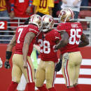 San Francisco 49ers running back Carlos Hyde, right, celebrates with quarterback Colin Kaepernick (7) and tight end Vernon Davis (85) after running for a 4-yard touchdown against the Washington Redskins during the fourth quarter of an NFL football game in Santa Clara, Calif., Sunday, Nov. 23, 2014. (AP Photo/Tony Avelar)