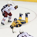 Nashville Predators center Filip Forsberg (9), of Sweden, passes the puck after he falls to the ice as he is defended by Columbus Blue Jackets defenseman James Wisniewski (21) in the second period of an NHL hockey game Saturday, Nov. 29, 2014, in Nashvill