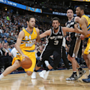 From left to right, Denver Nuggets guard Evan Fournier, of France, works the ball inside as San Antonio Spurs guard Marco Belinelli, of Italy, covers while Spurs guard Manu Ginobili, of Argentina, and Nuggets forward Anthony Randolph look on in the first