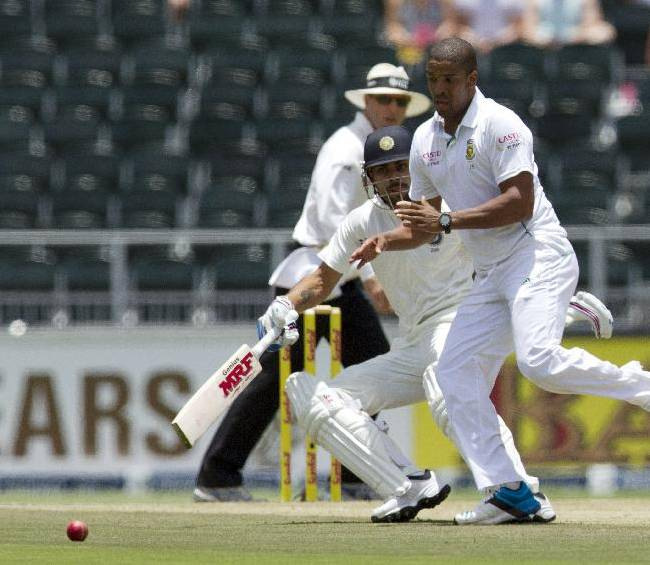 South Africa's bowler Vernon Philander, right, attempt fielding off his own bowling as India's batsman Virat Kohli, left, runs back home during the first day of their cricket test match at Wanderers stadium in Johannesburg, South Africa, Wednesday, Dec. 18, 2013