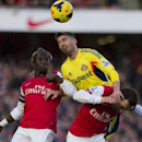 Arsenal's Bacary Sagna, left, and Santi Cazorla, right, fight for the ball with Sunderland's Fabio Borini, during their English Premier League soccer match, at Emirates Stadium, in London, Saturday, Feb. 22, 2014