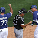 Los Angeles Dodgers' Joc Pederson (65) celebrates his two-run home run with Clint Robinson (73) as Chicago White Sox catcher Hector Gimenez stands near them during an exhibition baseball game in Glendale, Ariz., Friday, Feb. 28, 2014 The Associated Press