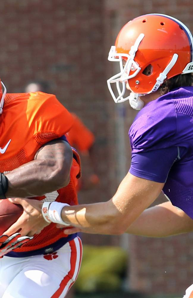 Clemson quarterback Cole Stoudt, right, hands off to running back D.J. Howard during the Tigers' NCAA college football practice on Wednesday, Aug. 6, 2014 in Clemson, S.C