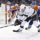 Los Angeles Kings Justin Williams (14) and Edmonton Oilers Andrew Ference (21) battle for the puck as goalie Ben Scrivens (30) protects the net during first period NHL hockey action in Edmonton, Canada, Sunday March 9, 2014 The Associated Press