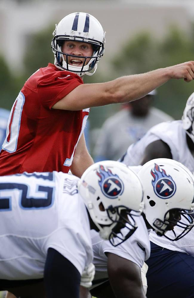 In this July 27, 2014, file photo, Tennessee Titans quarterback Jake Locker calls a play during NFL football training camp in Nashville, Tenn. The majority of teams pay their starting quarterbacks just a fraction of the base salaries of the Peyton Mannings, Tom Brady and Jay Cutler, who makes $17.5 million this season. The Titans declined to pick up the 2015 option on Locker because he has missed 14 of 32 games since being named the starter, and he's costing a mere $2 million in salary this season