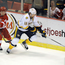 Nashville Predators left wing James Neal (18) keeps the puck away from Detroit Red Wings center Gustav Nyquist (14) during the first period of an NHL hockey game in Detroit, Saturday, Jan. 17, 2015 The Associated Press