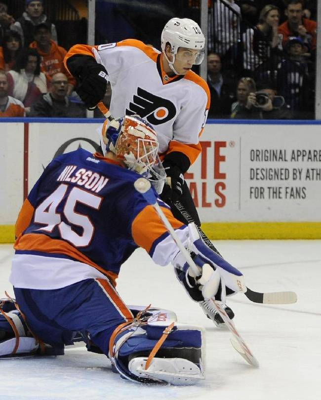 New York Islanders goalie Anders Nilsson (45) drives the puck away from the net as Philadelphia Flyers' Brayden Schenn (10) watches from behind in the first period of an NHL hockey game on Monday, Jan. 20, 2014, in Uniondale, N.Y