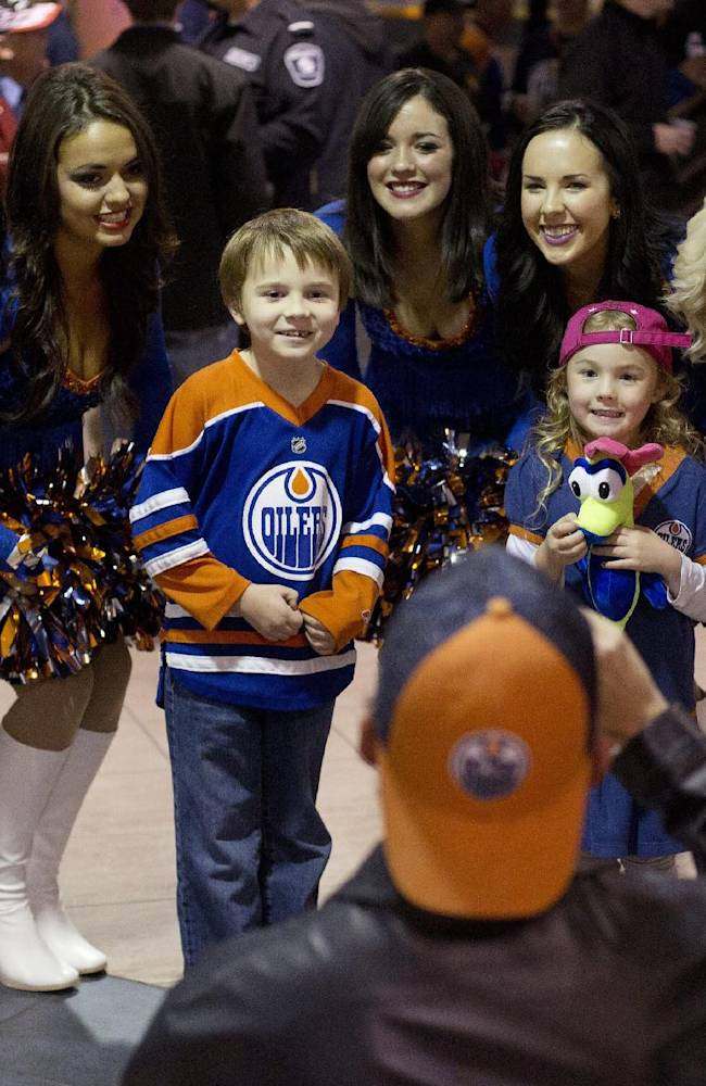 Young Edmonton Oilers fans get their photo taken with the Oilers cheerleaders in Edmonton, Alberta, on Tuesday, Oct. 1, 2013, before the Oilers' NHL hockey game against the Winnipeg Jets