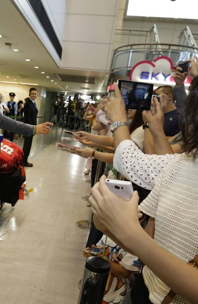 Kei Nishikori, left,  the second place winner of the 2014 U.S. Open tennis tournament,  greets his fans upon his arrival at Narita International Airport in Narita, near Tokyo, Saturday, Sept. 13, 2014. Nishikori was trying to become the first man from any Asian country to join the major singles champion club in tennis. Even if he didn't quite manage to do that, the Japanese right-hander demonstrated he has the stuff to contend by eliminating three of the top five seeded men: No. 1 Novak Djokovic, No. 3 Stan Wawrinka and No. 5 Milos Raonic