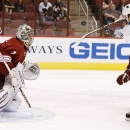 San Jose Sharks' Tomas Hertl (48), of the Czech Republic, tries to redirect the puck in the air in front of Phoenix Coyotes' Thomas Greiss (1), of Germany, during the first period in an NHL preseason hockey game on Friday, Sept. 27, 2013, in Glendale, Ariz. (AP Photo/Ross D. Franklin)